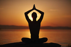 Enjoying yoga at sunset Stock Photography