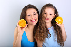 Enjoying young mother and cute long hair daughter holding slices Stock Photos