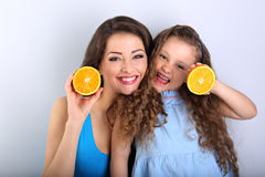 Enjoying young mother and cute long hair daughter holding slices Royalty Free Stock Image