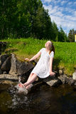 Enjoying a young woman. Enjoying young woman Young woman laughing and splashing with hes feet in the lake Royalty Free Stock Images