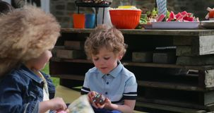 Enjoyiong a Chocolate Cupcake. Little boy and his friend sitting outdoors at a garden party. He is enjoying a chocolate cupcake