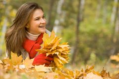 Enjoyment. Portrait of cheerful woman lying on autumnal land with maple leaves in hands Stock Images