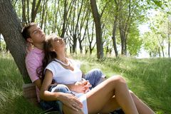 Enjoyment. Image of amorous couple having peaceful rest on green grass of park together Royalty Free Stock Photography