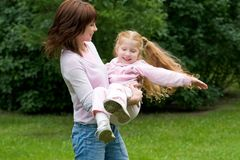 Enjoyment. Portrait of happy woman playing her ginger-haired daughter in park Stock Photos