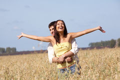 Enjoyment. Image of joyful girl stretching arms while being embraced by her boyfriend Stock Image