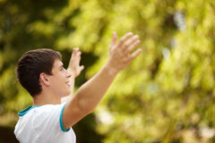 Enjoyment. Happy young adult on green foliage background, selective focus Royalty Free Stock Image