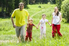 Enjoyment. Image of joyful family running over green field holding each other by hands in summer Stock Photography