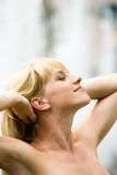 Enjoyment. Image of relaxed woman touching her hair with closed eyes and expression of pleasure on her face Stock Image