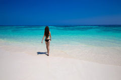 Enjoyment. Beautiful bikini woman walking on tropical beach, sli Royalty Free Stock Image