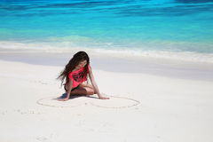 Enjoyment. Beautiful carefree brunette girl drawing heart on san. D in bikini relaxing on exotic beach beside blue water. Summer vacation. Attractive young woman Stock Image