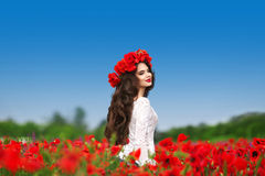 Enjoyment. Beautiful carefree brunette woman with long healthy h. Air running on red poppies field nature background. Wellness well-being happiness concept Stock Photography