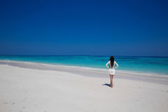 Enjoyment. Beautiful woman walking on exptic beach with white sa Stock Images