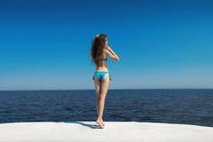 Enjoyment. Brunette bikini model woman posing over blue sky, out Stock Photography