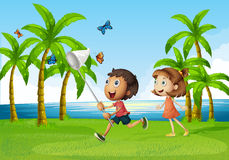 Enjoyment. Children trying to catch butterflyy in an open area Royalty Free Stock Photography
