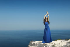 Enjoyment. Fashion Happy beautiful woman with dress over blue sk Stock Photos
