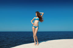Enjoyment. Fashion model woman in bikini over blue sky, outdoors Royalty Free Stock Photography