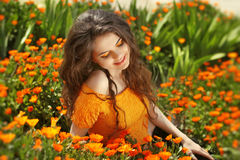 Enjoyment. Free Happy Woman Enjoying Nature. Freedom concept. Be. Auty Girl over marigold flowers field. Outdoors Royalty Free Stock Photos