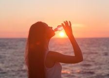 Enjoyment - free happy woman enjoying sunset. Asian Caucasian female model.Woman drinking from a Water Bottle at Sunset Royalty Free Stock Photo