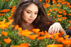 Enjoyment - free smiling woman enjoying happiness. Beautiful woman embracing in golden marigold flowers royalty free stock photo