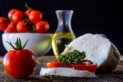 Enjoyment of Italian food. Tomatoes, olive oil and mozarella on a wooden table Stock Images