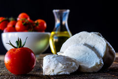 Enjoyment of Italian food. Tomatoes, olive oil and mozarella on a wooden table Stock Image