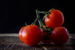 Enjoyment of Italian food. Wet tomatoes on an old table Stock Photos