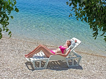 Enjoyment in life. A beautiful young woman in a bikini lying on a deck chair and sun on the beach of the Mediterranean Sea, photography Stock Photos