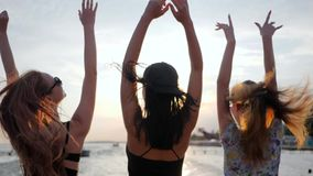 Enjoyment of life, happiness young women dance on background shiny sea in vacation, girls have fun on embankment, best