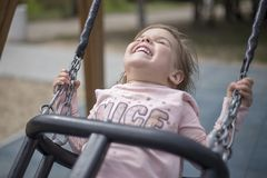 Enjoyment of a little girl from riding on a swing stock images