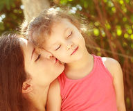 Enjoyment. Mother kissing happy kid Stock Photo