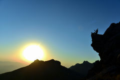 Enjoyment of a view of the sunrise on the rock Royalty Free Stock Photos