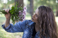 She enjoys the beauty and smells of this flower Royalty Free Stock Photos