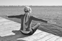 Enjoys nature, free time at the beach, gray tones. Freedom and healthy Lifestyle, blond resting, woman sitting, she stares at the water and city in the distance Stock Images