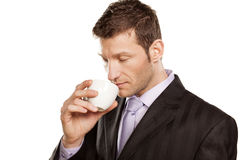 Enjoys the smell of coffee. Businessman enjoys the smell of his coffee on white background royalty free stock photography