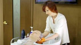 Enjuague del cliente del pelo en un salón de belleza metrajes