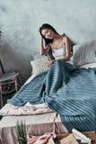 Enkel één meer minuut in bed Aantrekkelijke jonge vrouw die hand houden Royalty-vrije Stock Afbeelding