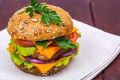 Enkel amerikansk hamburgare med cheddarost, kött och nya grönsaker Royaltyfri Foto