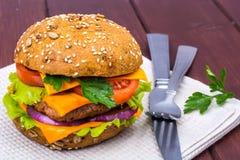Enkel amerikansk hamburgare med cheddarost, kött och nya grönsaker Royaltyfri Bild