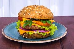 Enkel amerikansk hamburgare med cheddarost, kött och nya grönsaker Fotografering för Bildbyråer
