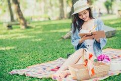 Enkel asiatisk tonårig picknick i parkeraläsningen arkivbild