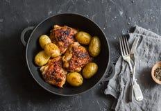 Enkel bakad höna med nya potatisar i en gjutjärnpanna på mörk bakgrund, bästa sikt royaltyfri fotografi