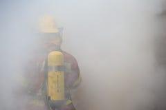 Enkel brandman i operationsurround med rök och damm Arkivbilder