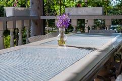 Enkel bukett av lösa blommor i en klar glass vas på en vit- och blåtttabell i en lantlig stil, solig dag Arkivbild