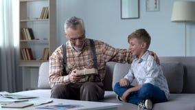 Enkel, der Großvater, der Aufmerksamkeit und der Sorgfalt für geliebte Geschenk gibt lizenzfreie stockfotos