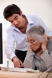 Enkel, der seine Großmutter unterrichtet Stockfotos