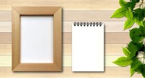 Enkel fotoram och vitanteckningsbok på wood bakgrund Fotografering för Bildbyråer