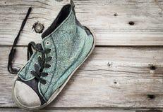 Enkel gammal blå sliten ut rinnande sko på wood bakgrund Arkivfoto