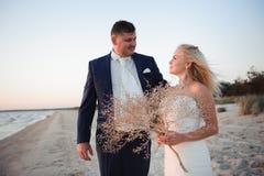 Enkel gehuwd Mooi jong paar op het strand bij zonsondergang stock foto
