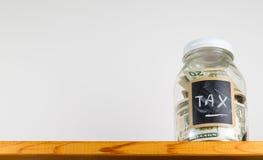 Enkel glass krus på trähyllan för sparande pengar Arkivbilder