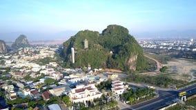 Enkel grön kulle för flyg- sikt med templet bland stad stock video